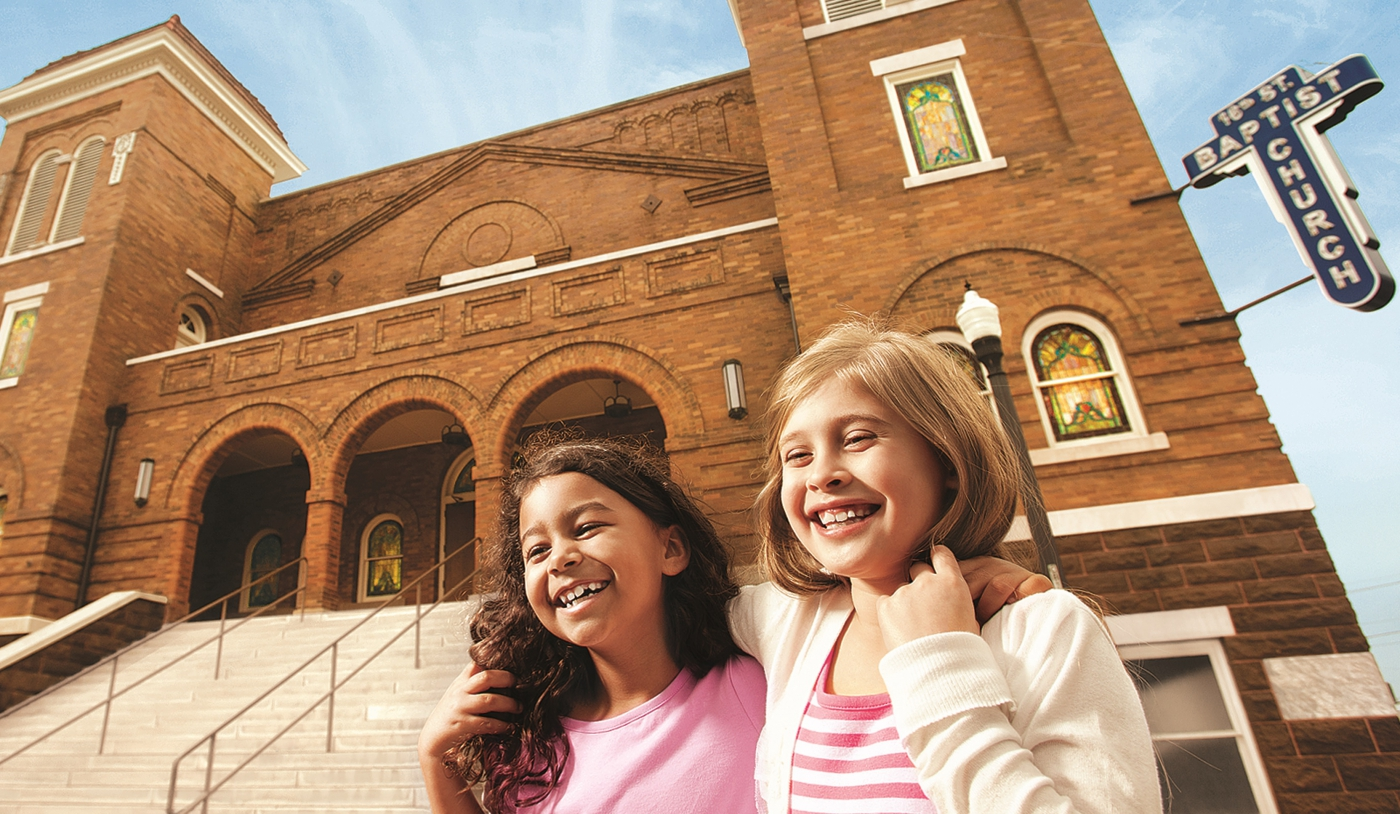 Two girls stand in front of the 16th Street Baptist Church, key in the Civil Rights Movement.